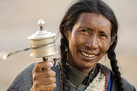 A tibetan man look in camera and play the pray wheel  Ngari Prefecture  Tibet province  China  Asia