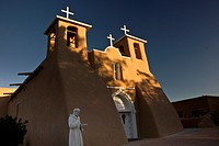 The first rays of sunlight on the bell towers of historic San Fernando de Assisi church in Taos, New Mexico
