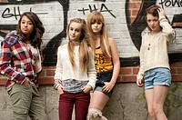 A group of 13 year old teenage girls moody with attitude standing in front of a graffiti covered wall UK