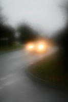 car driving in heavy rain on rural country road