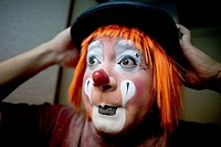 A clown puts on his bowler hat hat as he makes up in his hotel room before attending the 16th International Clown Convention: The Laughter Fair organi...