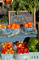 display at farmers´ market with cherry tomatoes in baskets in several colors, full-size tomatoes, large green peppers in basket, bunches of basil, bla...