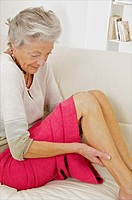 Senior woman holding her painful thigh on her sofa