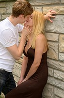 Man kissing a woman with eyes closed leaning against a stone wall