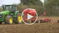 sowing wheat, mid shot of a tractor and seed drill coming through frame.