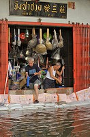 fighting a losing battle, two men desperately try to keep water out of their shop, bangkok floodings, chinatown, bangkok, thailand