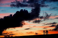 Silhouettes of three girls walking in the sunset