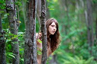 Nude Female model peeking from tree in forest near Lewiston Maine USA