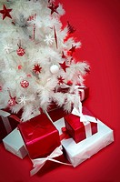 Still white Christmas tree with presents on red carpet.