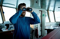 The captain of the container-vessel MV Flintercape uses binoculars to spot for other ships in the vicinity, during the voyage from Rotterdam, Netherla...