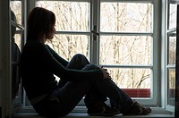 Woman silhouetted sitting on window ledge looking out of window