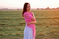Portrait of a beautiful young woman wearing summer dress standing in field looking away