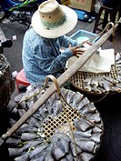 Fish seller with straw hat in Hua Hin street market, Thailand