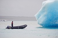 A man in a raft approaches an iceberg in Glacier Lagoon, Iceland