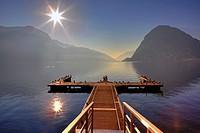 Jetty in the winter sun with seagulls in Lugano, Ticino, Switzerland, overlooking the mountain of Lugano, Monte San Salvatore