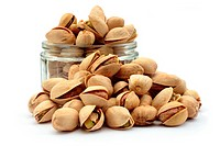 many pistachio nuts and a glass container. Isolated on a white background.