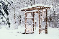 Winter garden arbor in falling soft snow, Midwest USA
