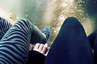 Legs of two girls sitting in the bank of a river, Ayora, Valencia, Spain