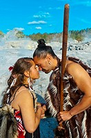 A Maori man with ta moko facial tattoo and woman doing hongi traditional Maori greeting with the Pohutu Geyser behind, Te Puia New Zealand Maori Arts ...