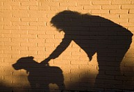 Shadow of woman and dog against brick wall