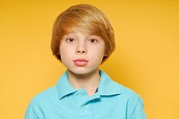 Eleven year old boy with expressive face and large eyes, looking straight ahead at the viewer and not smiling