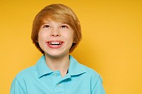 Cute eleven year old boy is smiling and looking up toward the top of the frame