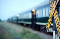 Blurred Rovos Rail passenger train passing by a Railroad Crossing, with the yellow warning sign about trains in the foreground, Southern Africa, Botsw...