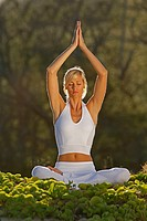 Attractive woman practices yoga at Makena, Maui, Hawaii