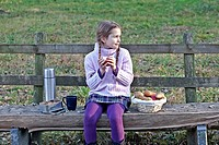 Girl sitting on a wooden bench in a meadow and picnicking