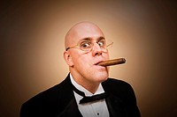 Middle-age bald man in a tuxedo, smoking a cigar