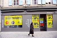 Stock photo of a woman walking past a French shop displaying sale signs.
