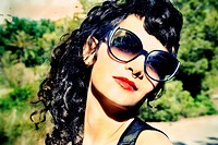Portrait of a girl with sunglasses and red lips with green trees behind.