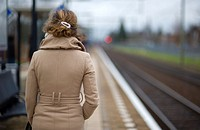 Oisterwijk, Netherlands. Young woman in waiting for her commuter-train from Oisterwijk to Tilburg, Netherlands on the platform of this small railway-s...