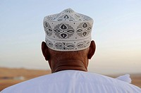 Middle East,Oman, Sharqiyah,Wahiba Sands,man wearing a hat watching the desert