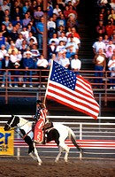 Cowgirl with American flag Cody Nite Rodeo Wyoming USA