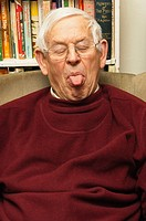 A senior elderly man in his 80´s pulling a funny face at home in England , Britain , Uk