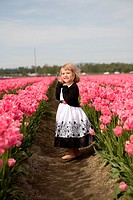4 year old girl in black and white dress playing and smiling in a tulip fields in Skagit Valley, Washington, USA