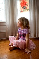 4 year old girl sitting on floor in her house looking off camera in a pink dress and purple shirt