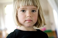 Portrait of a 4 year old girl in a black shirt with blond straight hair looking engagingly into the camera
