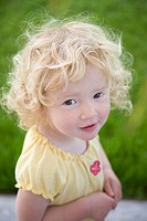 Portrait of a young girl with curly blond hair looking into the camera looking mischeivious