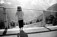 Young girl looking through a fence at a mountain scene in Mürren, Switzerland