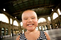 Young bald girl with pediatric cancer Leukimia looking happy and smiling in the Zurich train station, Switzerland