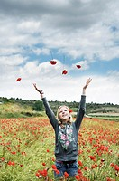 Blonde teen girl throwing flowers in the wind.