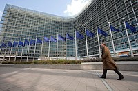 A man walks next to the Berlaymont building, the European Commission headquarters, in Brussels, Belgium