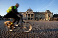 A man rides a bike next to the Royal Palace in Brussels, Belgium