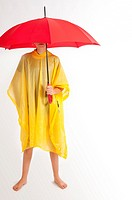 Teenage girl with yellow rain gear protected with red umbrella.