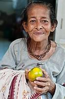 Widow with an orange in her hands, Ma Dham Ashram, run by NGO Guild of Service, Vrindavan, Uttar Pradesh, India