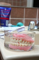 Kind of scary, isn´t it :-    an artificial denture of a senior in a glass of water in the bathroom with the toothbrush aside  Shallow depth of field ...