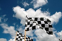 grand prix chequered flags flying in wind and blue sky