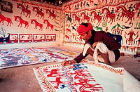 A tribal man ( Bhil tribe) is painting ( Rajasthan, India). This art form is called pithola painting.